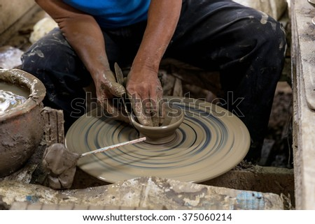 pottery man in blue shirt  to work his job