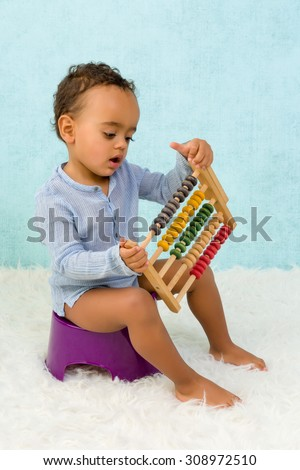 Potty training of a cute African toddler boy playing with an abacus - stock photo