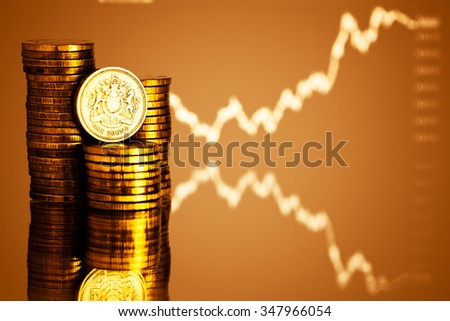 pound GBP coin and gold money. Fluctuating graph on red background. Rate of the pound sterling (shallow DOF)  - stock photo