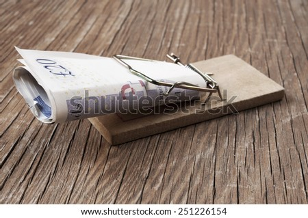 pound sterling bills in a mousetrap on a rustic wooden surface - stock photo