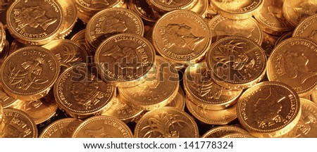 Pound sterling coins under tungsten lighting to create gold effect - stock photo