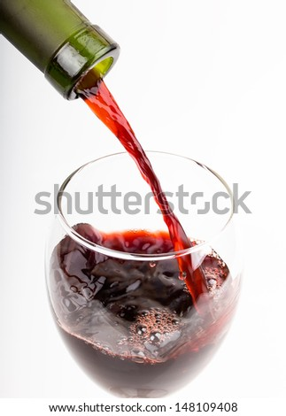 pour a glass of wine isolated on white background - stock photo