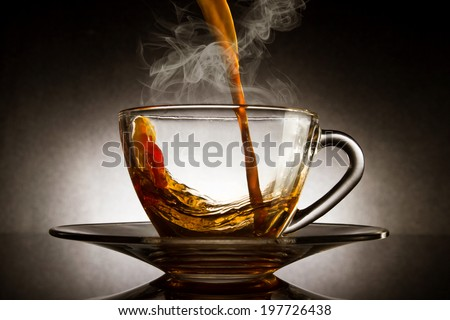 Pour coffee into transparent glass with steam cup on dark background. - stock photo