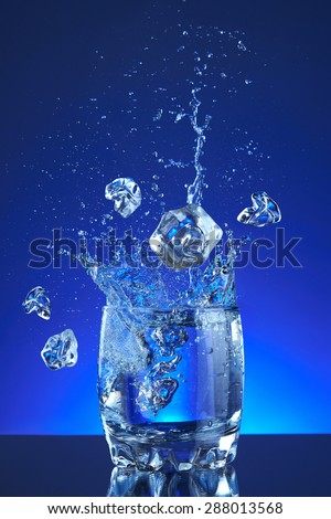 Pour fresh splash water on glass and ice cubes, blue background. Pitcher of water poured into a glass. Image refreshing water is poured and produces splashes and drops of water. Cool purity beverage.