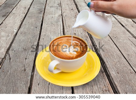 Pour milk to Coffee cup,hot drink, tea milk,milk in jug in wood background - stock photo