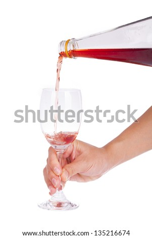Pour pomegranate juice into a glass on a white background.