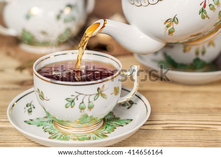 Pour tea into a cup. Vintage kitchen utensils. Shallow DOF - stock photo