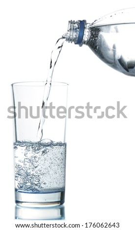 Pour water from bottle into  glass, isolated on white