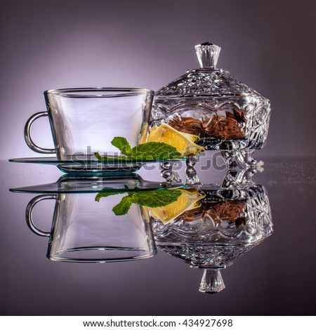 pour water in the cup with tea beg inside with lemon and mint leaf beside and also have cookies in the clear ceramic box with grey background  - stock photo
