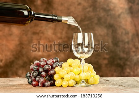 pour wine from bottle in shiny wine cup near grape - stock photo