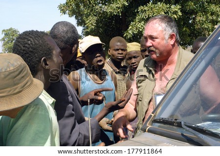 POURA, BURKINA FASO - JANUARY 3: mine in wild golden Poura a French trading some gold nuggets from gold diggers and calculates the price he can pay, january 3, 2008. - stock photo
