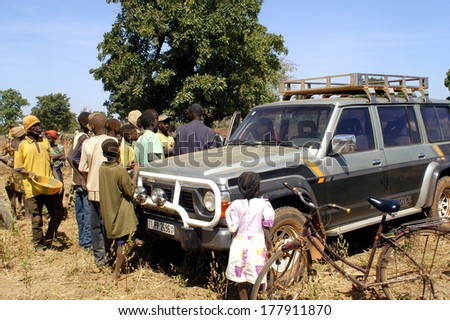 POURA, BURKINA FASO - JANUARY 3: mine in wild golden Poura a French trading some gold nuggets from gold diggers and a crowd forms around the car, january 3, 2008.