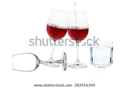 Poured red wine with drinking water on white background - stock photo