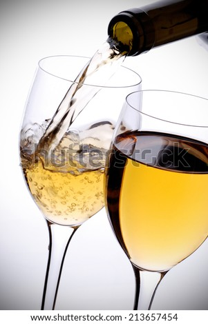 poured white wine on a white background - stock photo