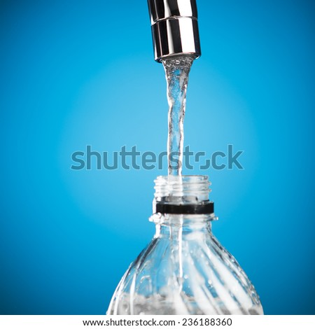 pouring a bottle of water from mixer tap - stock photo