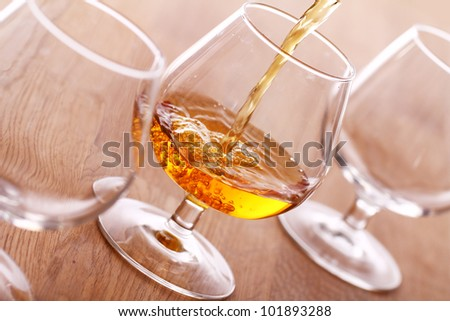 Pouring a cognac into the glass - stock photo
