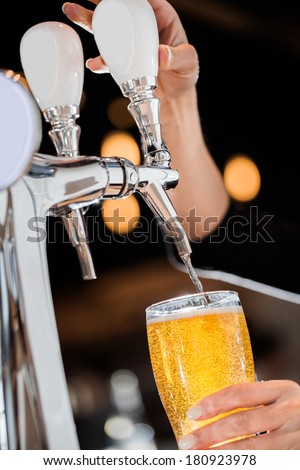 Pouring a Draft Blonde Beer in a Pint Directly from the Tap - stock photo