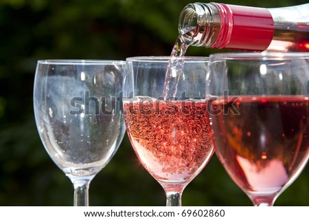 Pouring a pink wine into a glass.