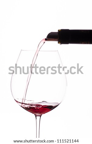 Pouring a red burgundy from a bottle into a wine glass