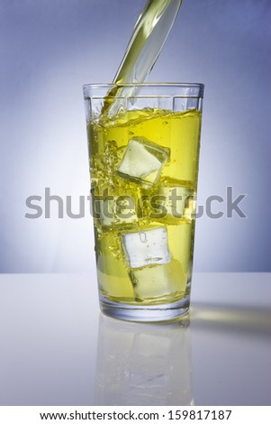 Pouring a refreshing beverage in a glass with ice.