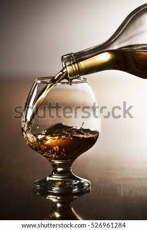 Pouring alcohol drink into glass close up shoot