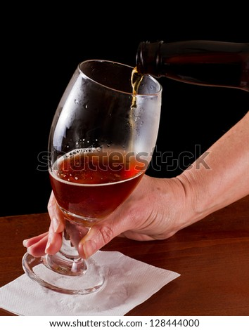 pouring an irish red ale beer into a chalice on a black background - stock photo