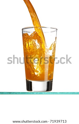 Pouring an orange beverage into a tall drinking glass. - stock photo