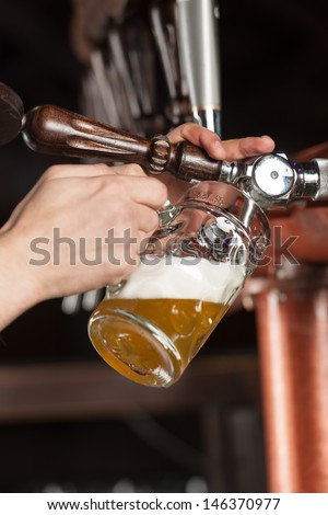 Pouring beer. Close-up of pouring beer at the pub
