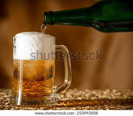Pouring beer from a bottle into a glass on a wooden table with a grain - stock photo