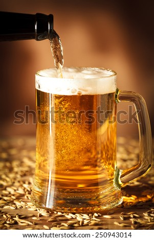 Pouring beer from a bottle into a glass. on brown background - stock photo