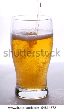 Pouring beer in the glass on white background