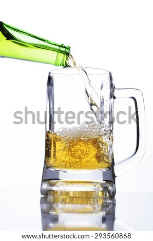 Pouring beer into a glass on white background for international beer days - stock photo