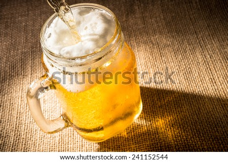 Pouring beer into a mason jar. - stock photo