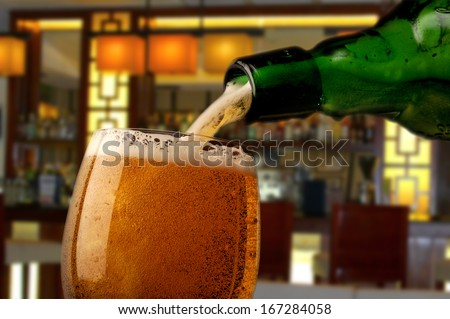 Pouring beer into glass with bar in background - stock photo