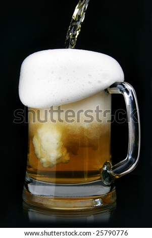 Pouring beer into mug over black background - stock photo