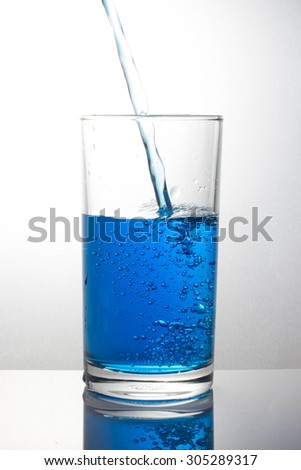pouring blue drink splash into glass on white background