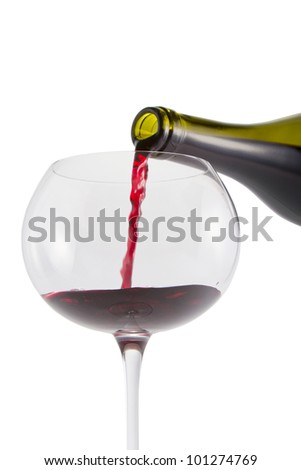 Pouring bottle of red wine into glass with clipping path