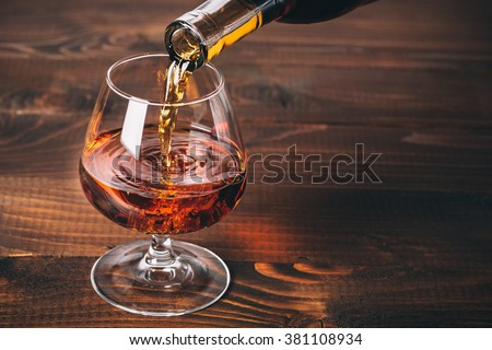 Pouring brandy or cognac from the bottle into the glass against wooden background - stock photo