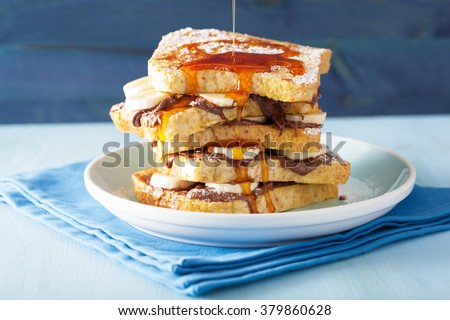pouring caramel over french toasts with banana chocolate sauce for breakfast - stock photo