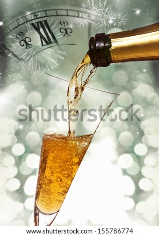 Pouring champagne against holiday lights, fireworks and clock close to midnight  - stock photo