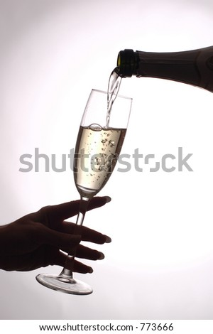 pouring champagne in glass - stock photo