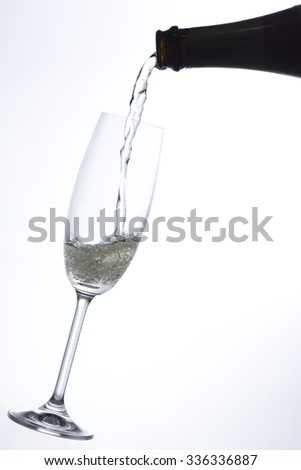 Pouring champagne into a glass in white background
