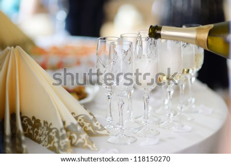 Pouring champagne into a glasses on a festive event - stock photo