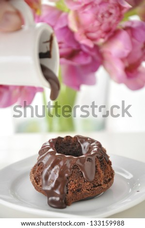 Pouring Chocolate Sauce on a Small Chocolate Cake with tulips in the background - stock photo