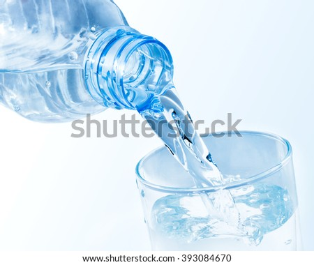 Pouring clean water from plastic bottle into a glass - stock photo