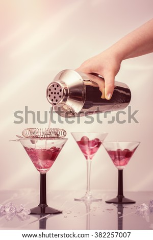 Pouring cocktail drinks from a shaker into Art Deco cocktail glasses