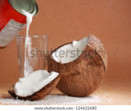 pouring coconut milk from a can into fresh coconut
