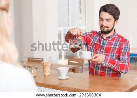 Pouring coffee. Portrait of man standing in coffee shop and pouring some espresso. - stock photo