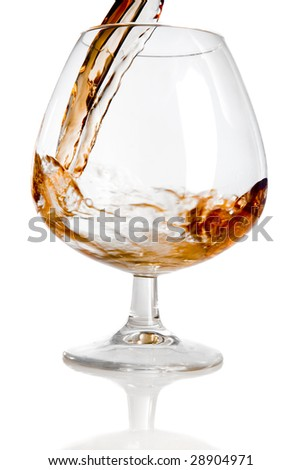 pouring cognac in glass on white ground - stock photo