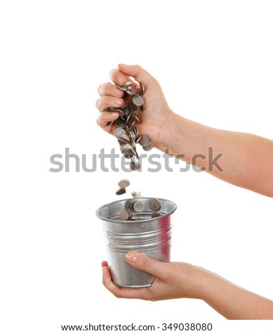 pouring coins into the bucket isolated on white background - stock photo